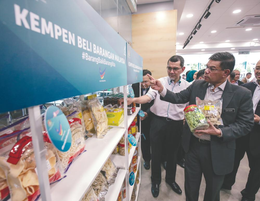 Syed Zainal Abidin (left) and Saifuddin looking at the special shelf at Kedai Mesra in Jalan Kolam Air Lama. – AMIRUL SYAFIQ/THESUN