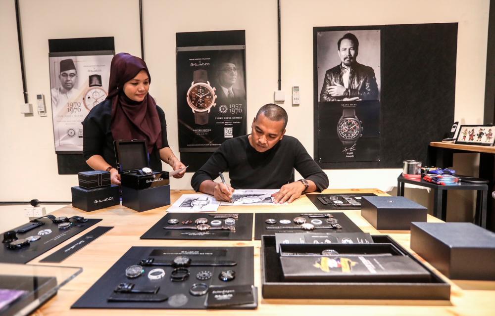 Zakiyah (left) watches over Bostami as he sketches his latest design. – ASHRAF SHAMSUL/THESUN