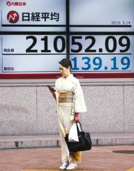File picture of a woman in front of an electronic board showing the Nikkei index outside a brokerage in Tokyo. The Nikkei 225 posted its second biggest slide so far this year. – REUTERSPIX