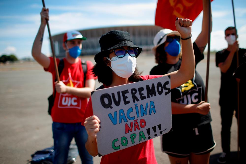 """Brazilians protest their country hosting soccer Copa America tournament amid the coronavirus disease (Covid-19) pandemic and against Brazilian President Jair Bolsonaro, in Brasilia, Brazil, June 13, 2021. The placard reads """"We want vaccines, not the cup"""". – REUTERSPIX"""
