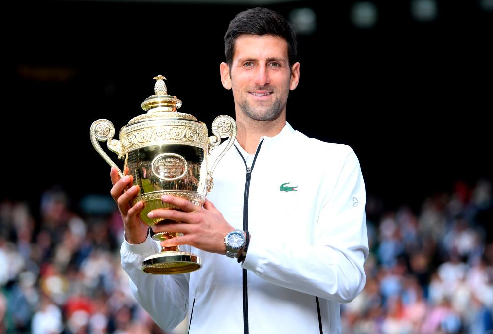 FILE PHOTO: Serbia's Novak Djokovic poses with the trophy as he celebrates winning the final against Switzerland's Roger Federer on July 14, 2019. – REUTERSPIX