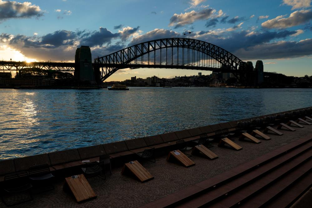 Harbour waterfront seating is devoid of people at sunset in front of the Sydney Harbour Bridge during a lockdown to curb the spread of a coronavirus disease (Covid-19) outbreak in Sydney, Australia, July 15, 2021. -Reuters