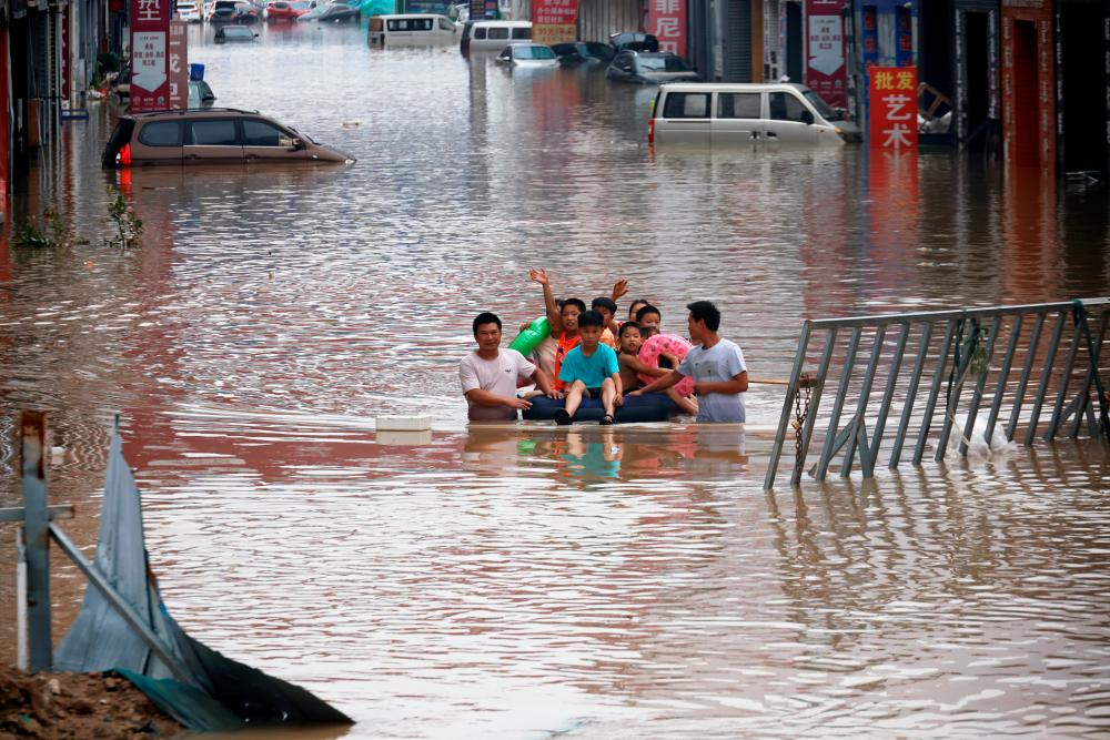 FILE PHOTO: Children sit on a makeshift raft on a flooded road following heavy rainfall in Zhengzhou, Henan province, China July 22, 2021. -Reuters