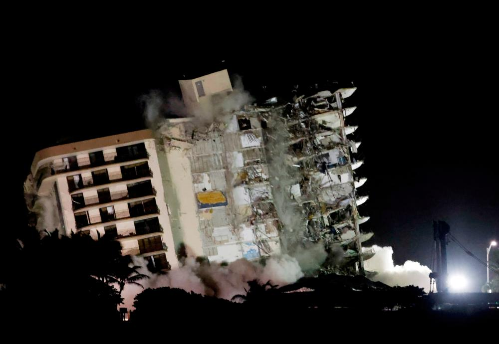 FILE PHOTO: The partially collapsed Champlain Towers South residential building is demolished, in Surfside, Florida, July 4, 2021. -Reuters