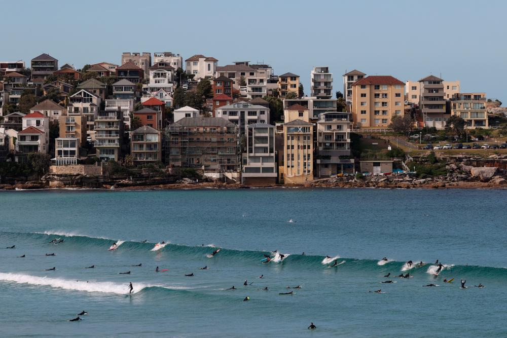 Surfers catch a wave at Bondi Beach during a lockdown to curb the spread of a coronavirus disease (Covid-19) outbreak in Sydney, Australia, July 27, 2021. - Reuters