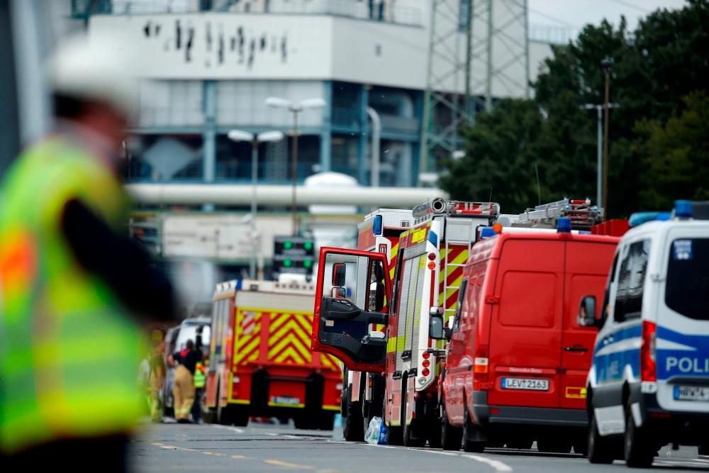 Firefighting trucks and vehicles are seen outside Chempark following an explosion in Leverkusen, Germany, July 27, 2021. - Reuters