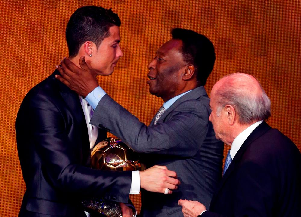 File Photo of Portugal's Cristiano Ronaldo (left) is congratulated by Pele (centre) after being awarded the FIFA Ballon d'Or 2013 in Zurich. – REUTERSPIX