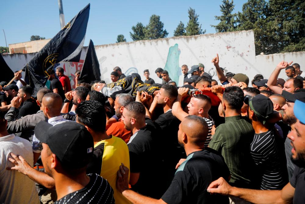 Mourners carry the body of Palestinian Osama Soboh, who was killed by Israeli forces during clashes in a raid, covered with Islamic Jihad flag, during his funeral in Burqin in the Israeli-occupied West Bank September 26, 2021. REUTERSpix