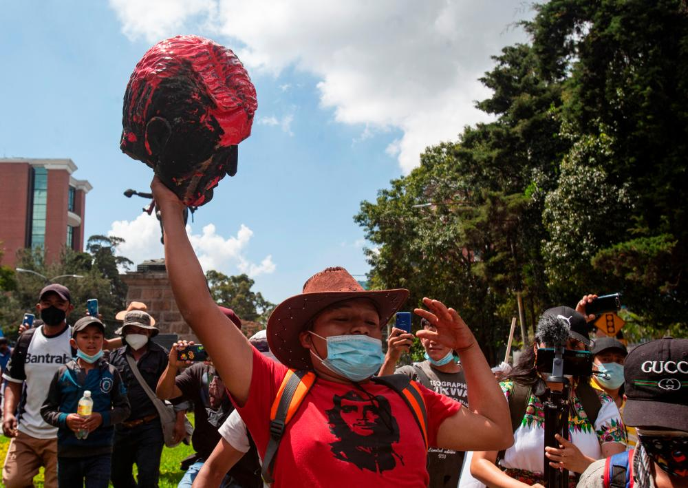 A demonstrator holds a head torn off from the statue of former President Jose Maria Reina Barrios during protests against the treatment of indigenous people by European conquerors, during Hispanic Heritage Day, in Guatemala City, Guatemala, October 12, 2021. REUTERSpix