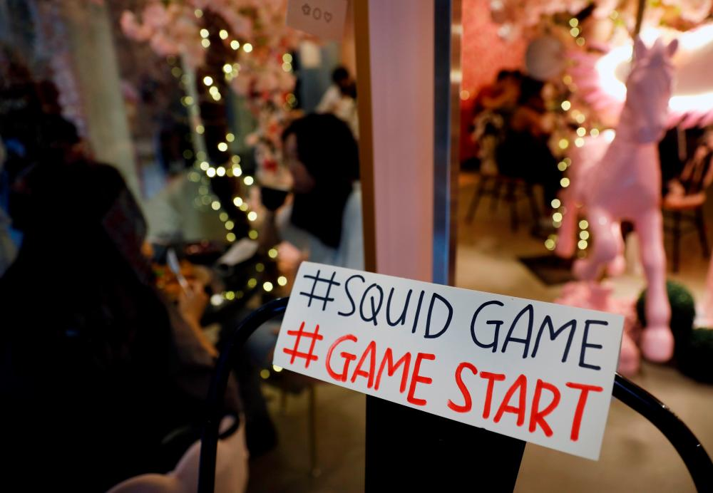 """A sign referring to the """"honeycomb challenge"""" featured in Netflix's new hit series """"Squid Game"""" is seen at Brown Butter Cafe in Singapore October 1, 2021. REUTERSpix"""