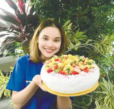 Farah with one of her creations, a large pavlova with strawberry cream and fresh fruits– Courtesy of Farah Azrooein Ghazali