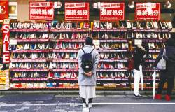 A woman looks at shoes on sale at an outlet store in Tokyo's shopping district. A survey shows 84% of consumers still use notes and coins for small purchases. – REUTERSPIX