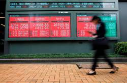 A woman walks past an electric screen showing world markets indices outside a brokerage in Tokyo, Japan, July 1, 2019. REUTERS/Issei Kato