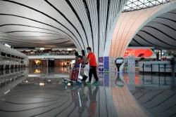 Passengers wearing face masks following the coronavirus disease (COVID-19) outbreak walk with luggages at a terminal hall of the Beijing Daxing International Airport ahead of Chinese National Day holiday, in Beijing, China September 25, 2020. Picture taken September 25, 2020. REUTERS/Carlos Garcia Rawlins