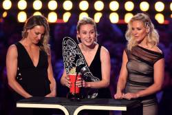 "US actress Brie Larson, flanked by her stunt doubles Joanna Bennett and Renae Moneymaker, accepts the award for Best Fight for ""Captain Marvel"" during the 2019 MTV Movie & TV Awards at the Barker Hangar in Santa Monica on June 15, 2019."