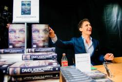 "David Lagercrantz, author of the final three novels in the Millennium series, originally by Stieg Larsson, signs copies of ""The Girl in the Spider's Web"" at a bookstore in Stockholm. Lagercrantz was commissioned to continue the saga after Larsson's death. © JONATHAN NACKSTRAND / AFP"