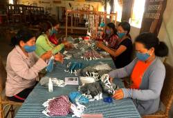 Weavers from the Maybank Women Eco-Weavers programme in Cambodia packing the finished handwoven masks to be shipped out for distribution.