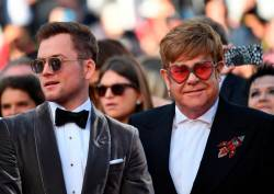 "British singer-songwriter Elton John (R) and British actor Taron Egerton (L) arrive for the screening of the film ""Rocketman"" at the 72nd edition of the Cannes Film Festival in Cannes, France, on May 16, 2019. © Alberto PIZZOLI / AFP"