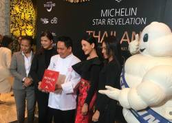 In this photo taken on November 11, 2019, Thai chef Chumpol (3rd L) holds the two Michelin stars award during a ceremony in Bangkok. Two traditional cuisine restaurants that have been awarded two Michelin stars, a first for the gastronomy of this Asian country renowned throughout the world. / AFP / Stéphane DELFOUR