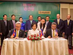 (From left, seated) Maybank Cambodia CEO Datuk Mohd Hanif Suadi, Chea Serey and Hamirullah Boorhan signing the MoU, presided over by NBC deputy governor Dr Sum Sannisith (standing, fourth from left) and witnessed by management members of NBC and board of Directors of Maybank Cambodia.