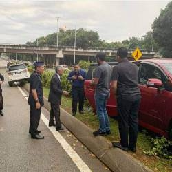 Yang di-Pertuan Agong Al-Sultan Abdullah Ri'ayatuddin Al-Mustafa Billah Shah (2nd from L) stops by the scene of an accident.