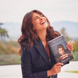 Priyanka holding up a copy of her memoir, Unfinished.