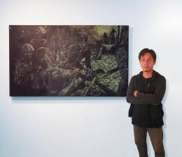 Faiz with his painting titled 'Invasion'.