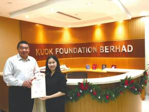 Kuok Foundation general manager Ng Teck Seng presents a scholarship to a student.