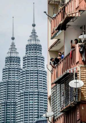 Residents of the Selangor Mansion flats in Kuala Lumpur watch security operations on the ground after their building and another one in the vicinity was placed under an enhanced movement control order. Sunpix by ADIB RAWI YAHYA