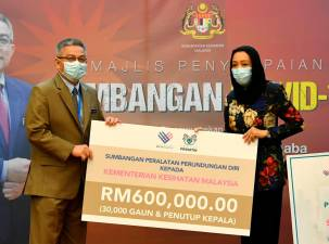 Health Minister Datuk Seri Dr Adham Baba (L) receives a donation of RM600,000 worth of PPPE from the MyPrihatin Foundation presented by its chairman Prof Datuk Halimaton Hamdan at the Covid-19 Fund donation ceremony at the Ministry of Health today. - Bernama