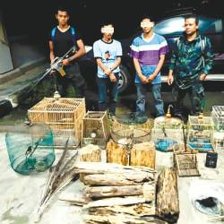 Rangers guarding two suspected poachers and some seized items.