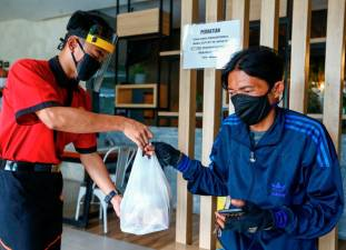 "A waiter wearing a face shield and a protective mask hands takeaway food to a man at a restaurant, as the Indonesian capital kicks off a two-week ""transitional"" period of easing restrictions, after the pace of coronavirus disease (COVID-19) infections slowed over the last two weeks, in Jakarta, Indonesia, October 12, 2020. REUTERS/Ajeng Dinar Ulfiana"
