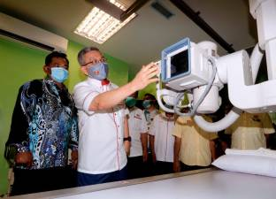 Health Minister Datuk Seri Adham Baba (2nd from L) looks closely at the digital X-ray machine after witnessing the handover of the health clinic construction project in Batu Berendam, Malacca today. - Bernama