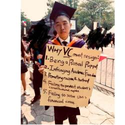 Wong Yan Ke with the protest placard that he carried on stage when receiving his scroll.