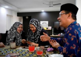 Tengku Shawal, a royal descendant, talks as his daughter Tengku Puteri (L) and his sister Tengku Intan (C) reminisce over old family photos at Intan's home in Singapore August 21, 2020. Picture taken August 21, 2020. REUTERS/Edgar Su