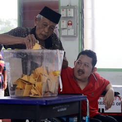 Sadiman Mortomo, 81, helps his disabled son Zulkifli Sadiman, 56, (right) to cast a vote at the Tanjung Piai by-elections today. — Bernama