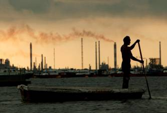 FILE PHOTO: A fisherman rows his dinghy past oil refineries near port terminals in Singapore November 5, 2013. REUTERS/Edgar Su/File Photo/File Photo