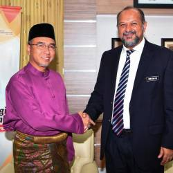 Communications and Multimedia Minister Gobind Singh Deo greets Malacca Chief Minister Adly Zahari during a visit to Seri Negara today. - Bernama