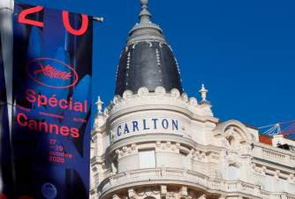 "The official poster for the ""Cannes 2020 Special"" event is seen in front the closed Carlton Hotel on the Croisette in Cannes, France, October 27, 2020. The event, which will run from October 27 to 29, is a slimmed down version of 2020's Cannes Film Festival, five months after the cinema showcase was cancelled due to the coronavirus disease (COVID-19) outbreak. REUTERS/Eric Gaillard"
