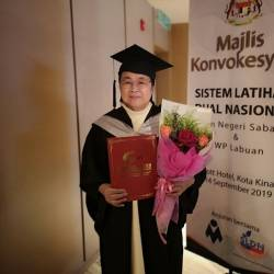 Sister Rufina with her certificate and a bouquet during the Sabah and Labuan FT National Dual Training System convocation yesterday. — Borneo Post
