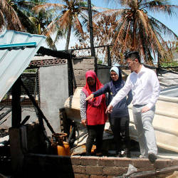 Malaysia Games (Sukma) 2019 handball athlete Nur Fazira Mohd Nor (centre), and her mother Hanisah Din (left), showing the remains of their house that was burnt down to the Perak state Youth and Sports Development Committee chairman Howard Lee Chuan How. — Bernama
