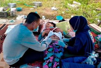 An injured woman is treated in a makeshift hospital in Majene on January 17, 2021, after a 6.2-magnitude earthquake rocked Indonesia's Sulawesi island. / AFP / Aswan Aprianto
