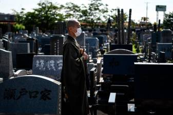 This photo taken on June 16, 2020 shows Yogetse Akasaka, a Buddhist monk and beatbox musician, posing at a cemetery after a religious ceremony in Shimoshizu, Chiba prefecture. / AFP / CHARLY TRIBALLEAU /