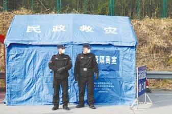 Security personnel stand in front of a disaster relief tent at a checkpoint in Yunxi county, Hunan province, near the border to Hubei province. – Reuterspix