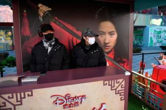 "Two workers wearing face masks manning a promotional stand for the Disney move ""Mulan"" in an almost empty shopping mall in Beijing."