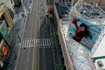 "FILE PHOTO: A poster of the Walt Disney Studios' ""Mulan"" movie, which was going to be released on March 27, towers over an empty Hollywood Boulevard during the global outbreak of coronavirus disease (COVID-19), in Hollywood, Los Angeles, California, U.S., March 31, 2020. REUTERS/Lucy Nicholson/File Photo"