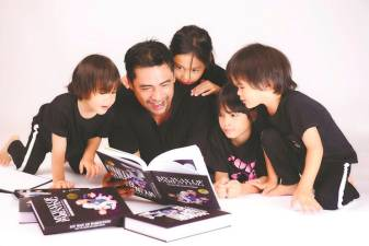 Sheikh Muszaphar reading his new book with his family. –Courtesy of Datuk Dr Sheikh Muszaphar Shukor