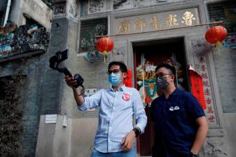 Paul Chan, tour guide and CEO of Walk in Hong Kong, and Charles Lai, architect, speak during a live streamed virtual tour, following the coronavirus disease (COVID-19) outbreak in Hong Kong, China August 16, 2020. Picture taken August 16, 2020. REUTERS/Tyrone Siu