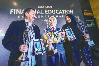 From left: SK Kerubong headmaster Hazman Dolah, Nur Khairina and Jamilah during the awards ceremony in Kuala Lumpur yesterday. – Adib Rawi Yahya/theSun