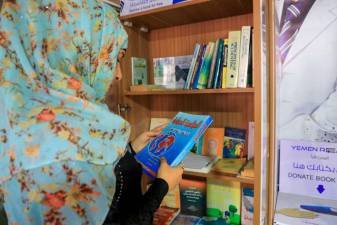"A Yemeni woman checks out a book from a mini-library, put in place by ""Yemen Reads"" campaign, in the capital Sanaa on September 29, 2020. / AFP / Mohammed HUWAIS"